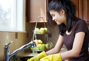 Teen girl washing dishes at kitchen sink